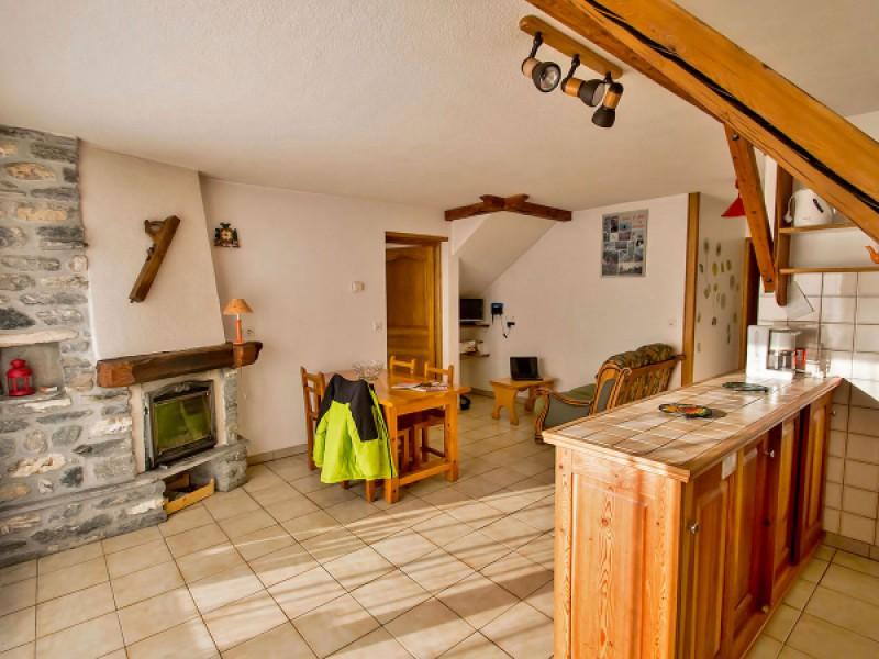 La salle à manger avec cheminée et coin cuisine